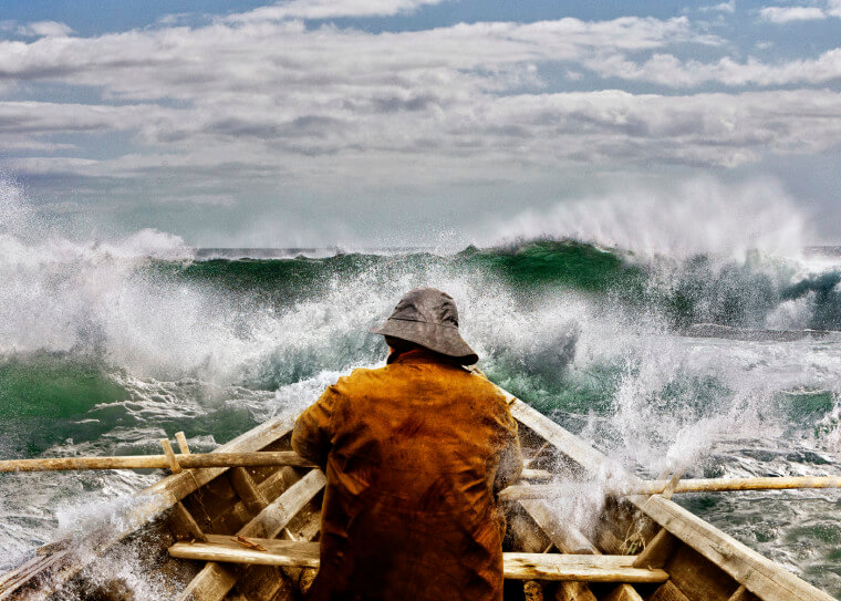 Old man and the sea, in a rowboat or skiff paddling and fighting the waves of the ocean.